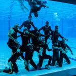 Freedivers have fun in aqua lublin behind glass making pyramid